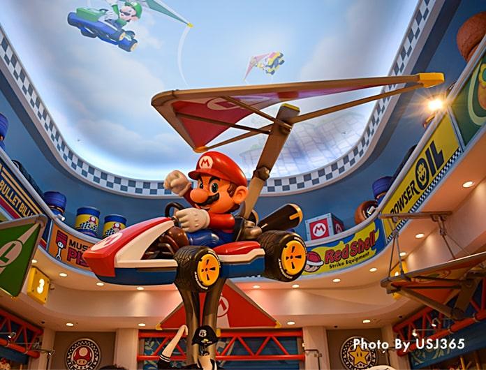 カートに乗ってグライダーで空を飛ぶマリオ